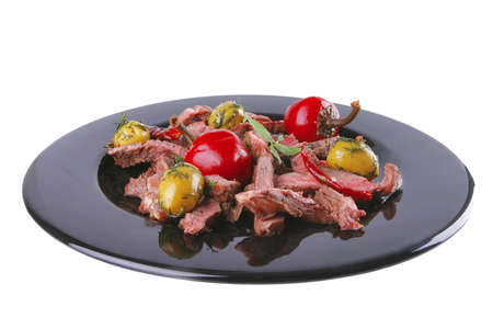 roast meat slices served on black dish over white photo