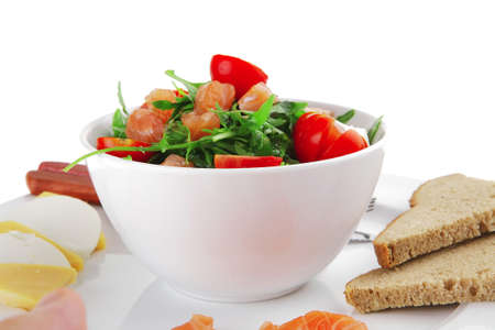 fresh green salad with smoked salmon in white bowl photo