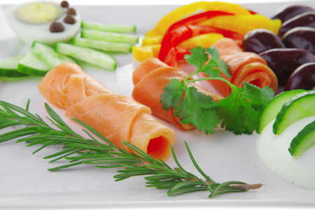 smoked salmon rolls on white plate with rosemary photo