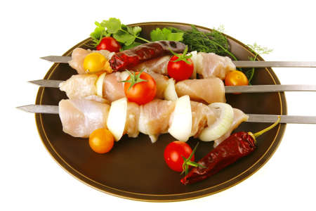 fresh raw chicken kebabs served with vegetables photo