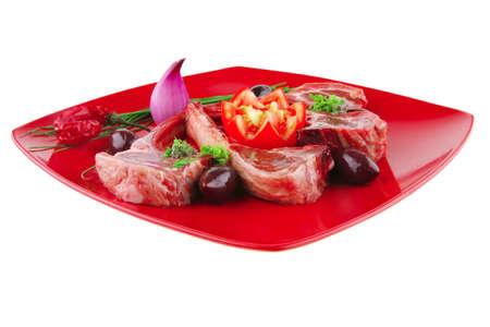 adn: costillas servido sobre una placa roja con tomates y verdor  Foto de archivo
