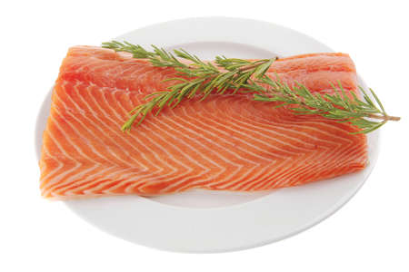 salmon steak: fresh raw red fish fillet on white plate and rosemary Stock Photo
