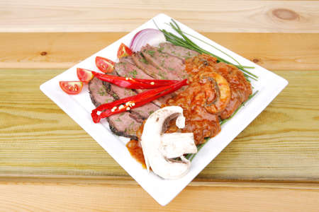 beef on plate with vegetables over wooden table photo