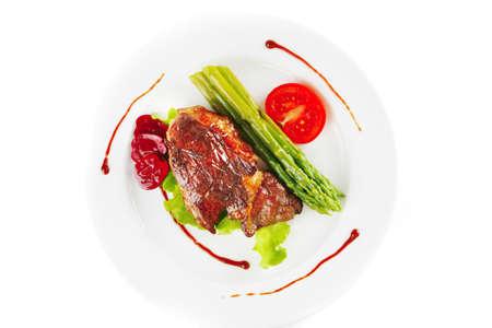 bistecche: carne di manzo servito su una piastra bianca con asparagi