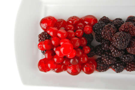cherry and wild berrys over white dessert plate photo