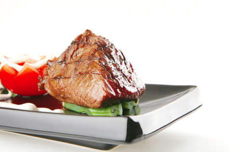 juice roast fillet mignon served on a black plate with tomato photo