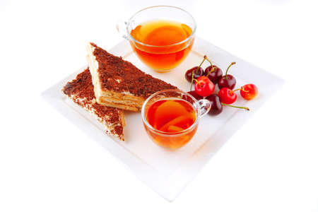 tea and cherry with cakes on white plate photo
