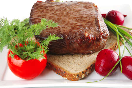 red meat on bread with vegetables on white photo