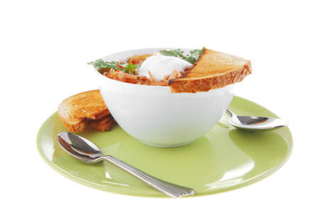 image of vegetable soup with spoon and sour cream photo