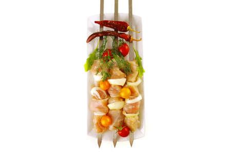 fresh chicken shish kebab on long white plate photo