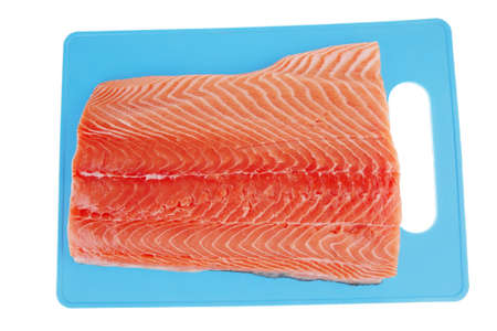 raw salmon fillet on blue plate over white photo