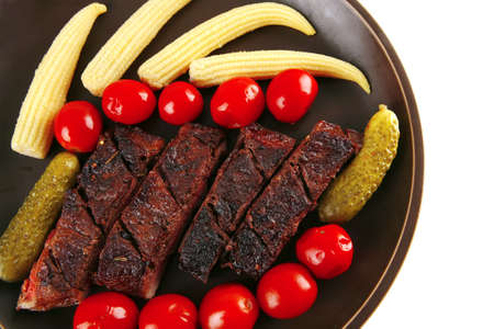 meat served with baby corns on dark plate photo