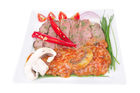 beef on plate with vegetables over white  photo