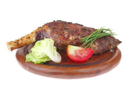 meat savory on wooden plate: roast shoulder with tomato and chives isolated on white background photo