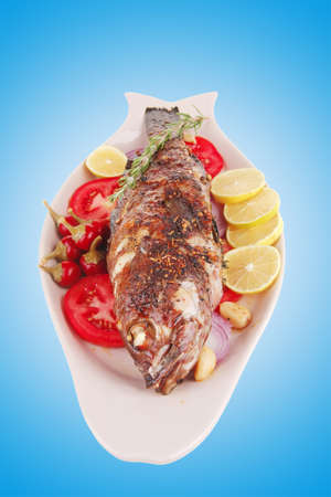 fryed: whole fried bass on plate, served with lemons and tomatoes