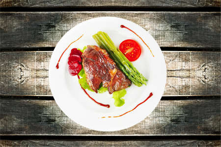 roasted beef meat served with asparagus on plate photo