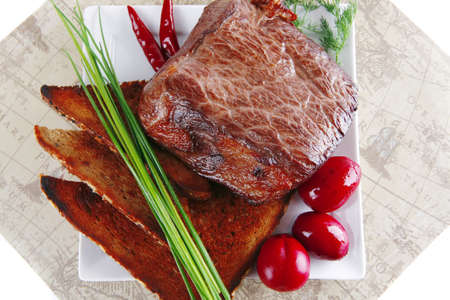 beef served with vegetables on white plate with placement photo