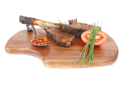 meat savory on wooden plate: roast ribs with peppers tomato and dry spices isolated on white photo