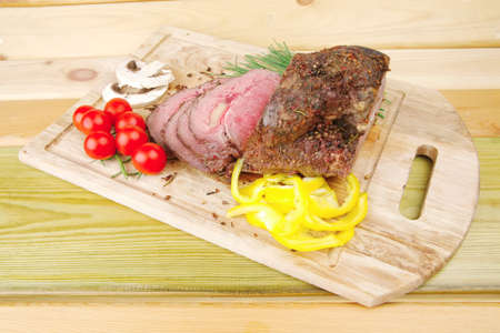 grilled barbecue on wooden plate with vegetables photo