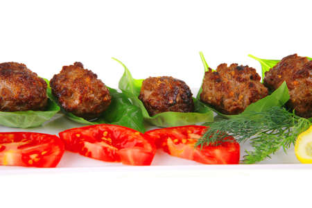 grilled french meat balls with tomatoes on white photo