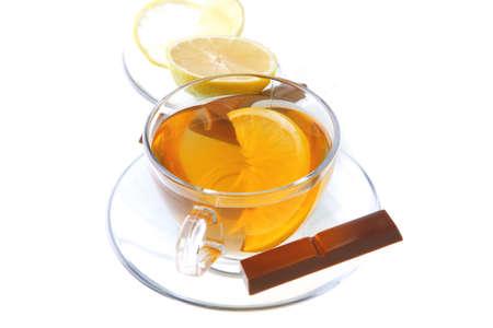 lemon and tea with chocolate on transparent dishware photo