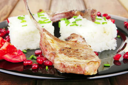 meat food: ribs on black with rice garnich and tomatoes on black on wood Stock Photo - 8462069
