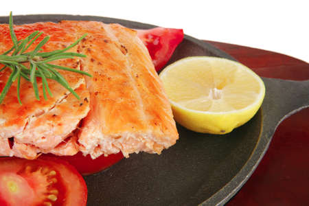 food: grilled salmon on iron pan over wooden plate isolated on white background Stock Photo - 8497094