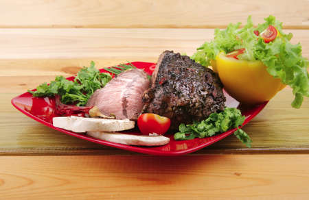 beef slice on red plate and vegetables on wood photo