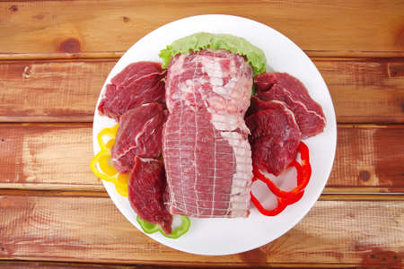fresh red meat with vegetables on wood photo