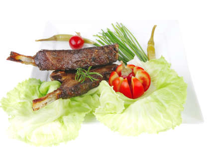 meat savory: roast ribs on white plate with peppers lettuce tomato and chives over white background photo