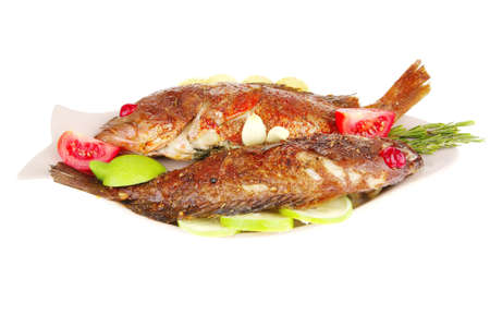 roasted sea fish on plate with tomatoes, lemon and rosemary
