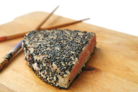 served roasted tuna chunk in black sesame on wooden plate isolated over white background photo