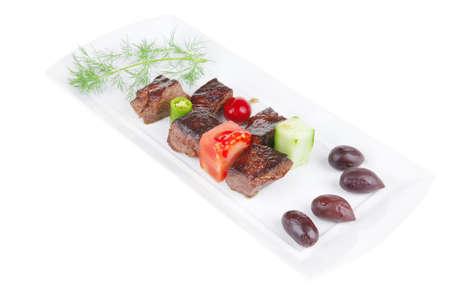 european food: alimentaria europea: a la gulash de carne en un plato blanco con tomate crudo, eneldo y aceitunas