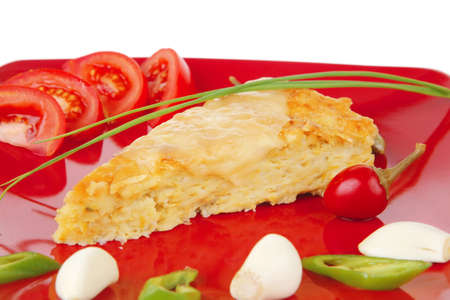 food : vegetable casserole piece over red plate ready to eat with chives tomatoes peppers and chives isolated over white . shallow dof photo