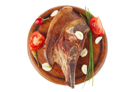 fresh hot roasted beef meat bone steak on red wooden plate with red hot pepper and capers isolated over white background Stock Photo - 8682070