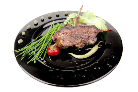 cooked pepper ball: served main dish : lamb meat ribs on plate with hot peppers and capers on black plate isolated over white background