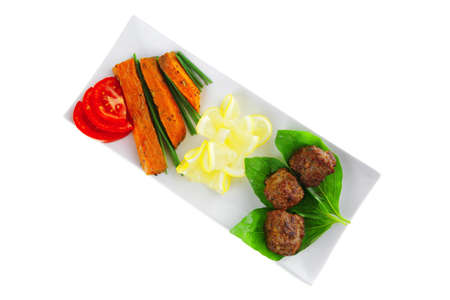 meatballs with tomatoes and lemon on basil leaf photo