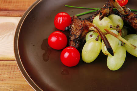 meat ribs on dish with tomatoes on table photo