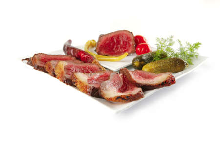 grilled beef slices and vegetables on white plates . isolated over white . shallow dof photo
