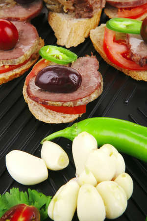 snakes on grill plate : tartlets with sliced meat and supplements isolated over white background . shallow dof photo