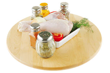 pepper castor: fresh chicken drumstick on wooden plate over white