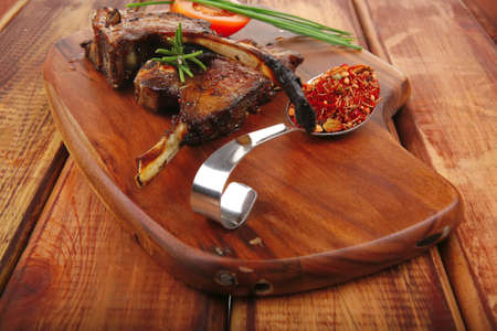 savory plate on wood : grilled ribs on plate with chives and tomato isolated on wooden table photo