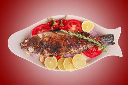 main course: whole fryed sunfish on plate with lemons and peppers photo