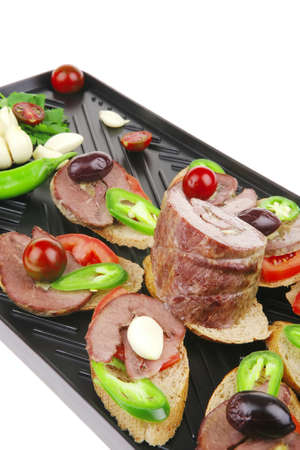snakes on plate : tartlets with meat and vegetables isolated on white . shallow dof photo