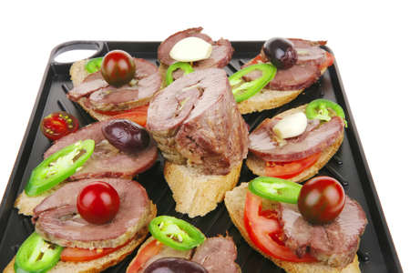 snakes on black grill plate : meaty tartlets with supplements isolated over white background photo