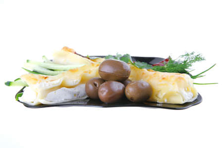 cheese cannelloni served with pepper and olives on black plate photo