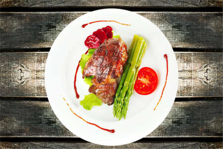 bar top: roasted beef meat served with asparagus on plate Stock Photo