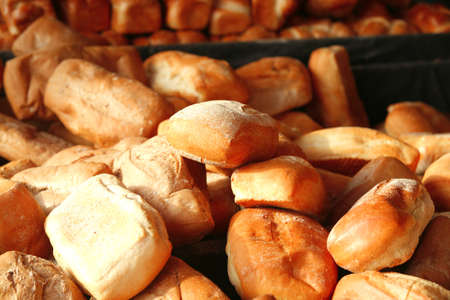 fresh lot of baked buns on counter, illuminated by the sun . shallow dof photo