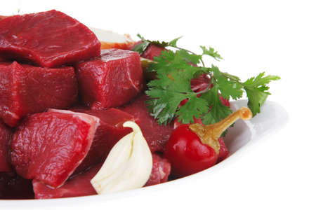 circular muscle: slices of raw fresh beef meat fillet in a white bowls with garlic and red peppers isolated over white background