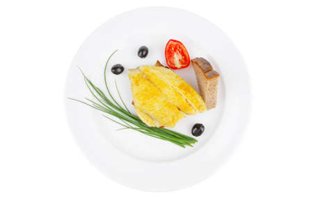 served fish fillet with greek olives,tomatoes,chives and lemon over white plate photo